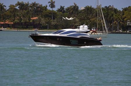vicinity: Sleek black motor yacht cruising the florida intracoastal waterway in the vicinity of miami beach Editorial