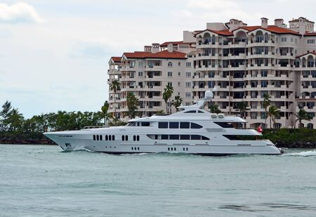 Mega motor yacht cruising by luxury island condos on its way to the open ocean.