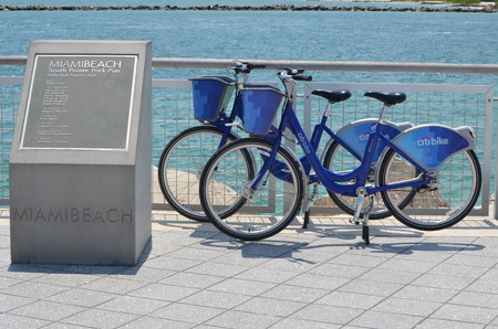 Rental bicycles parked at a fishing pier in Miami Beach.  Rental bikes can be picked up and dropped off a various locations.They can be rented by the hour and have become increasingly popular with tourists and local residents.