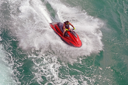 Angled overhead view of a man speeding on a red jet ski