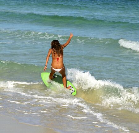 skim: Young woman surfing on a skim boat Stock Photo