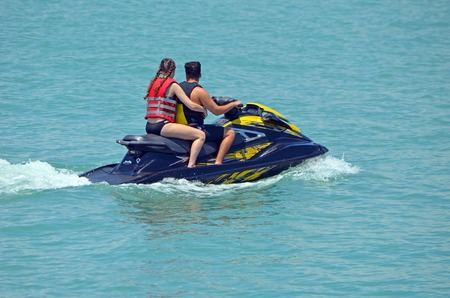 Young couple riding tandem on a jet ski
