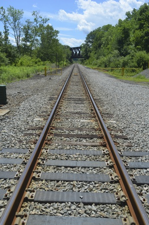 Railroad tracks in rural western Connecticut going under a trestle in the far distance Фото со стока