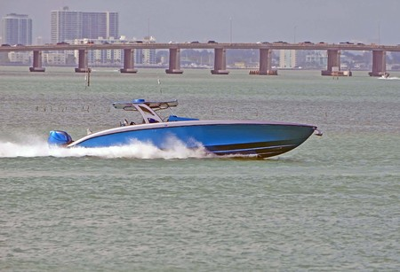 Upscale speed motor boat racing acrosss the florida intra-coastal waterway off Miami Beach with a Julia Tuttle Causeway bridge in the background. Stock Photo - 86125746