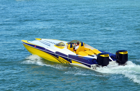 Sleek aerodynamic speed boat powered by two outboard engines.