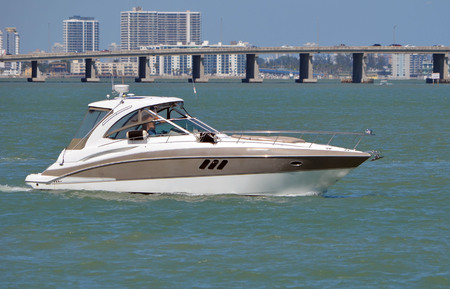 Upscale cabin cruiser on the florida intra-coastal waterway off Miami Beach with a Julia Tuttle causeway bridge in the background. 스톡 콘텐츠