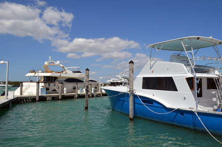 Luxury motor yacht and a charter deep-sea fishing boat moored at a marina on Haulover Inlet in southeast florida