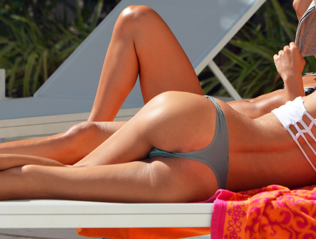 Curvaceous woman sunning in a thong bikini,