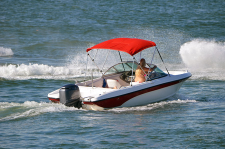 Sporty runabout motorboat with a red canvas canopy and a single outboard motor. Redactioneel