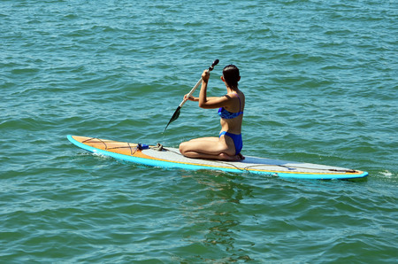 Attractive young woman on a paddle board .