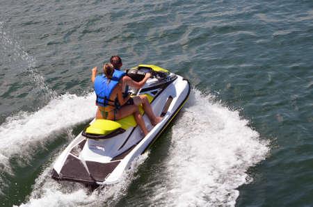 Couple riding tandem on a speeding jetski Banque d'images