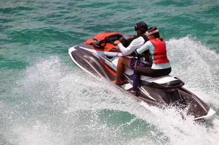 Young couple riding tandem on a speeding jetski.