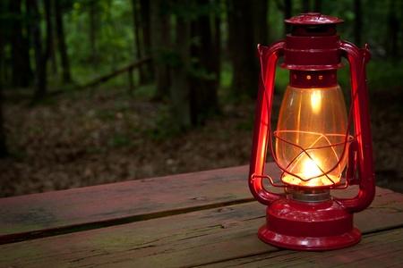 Gloeiend verlichte rode lantaarn op een picknicktafel in de schemering. Stockfoto
