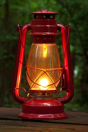 Glowing lit red lantern on a picnic table at dusk.