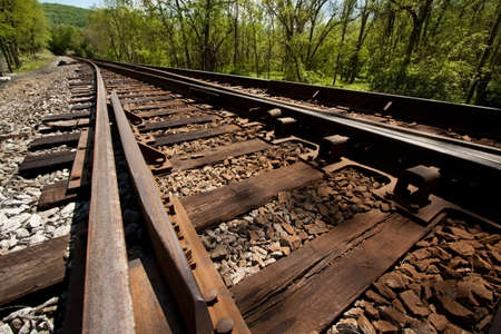 Angled view down railroad tracks in a country setting