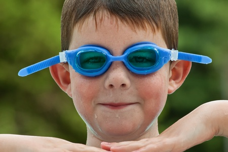 Boy in blue swim goggles having a fun time at the pool Stock Photo - 9978671