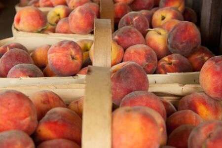 Baskets of fresh peaches at a produce stand
