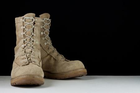 botas: Par de botas de cuero marr�n de combate del Ej�rcito colocados en posici�n inclinada sobre un fondo negro. Foto de archivo