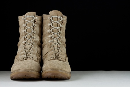 acu: Pair of tan leather Army combat boots side by side on black background.