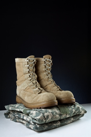 Angled photo of a apir of tan leather Army combat boots placed together on camouflage uniform on black background. Stock Photo