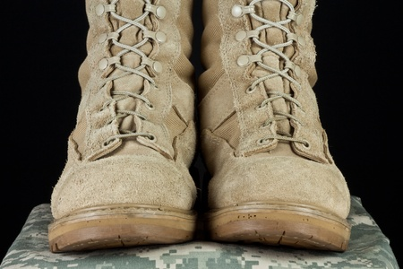 Pair of tan leather Army combat boots placed together on camouflage uniform on black background.
