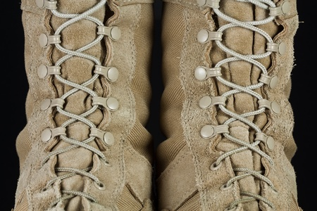 Close-up of tan leather Army combat boot laces on black background.