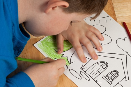 Young boy in blue shirt coloring a picture with pencils while laying on the floor