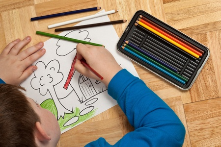 Young boy in blue shirt coloring a picture with pencils while laying on the floor  Stock Photo - 13252614
