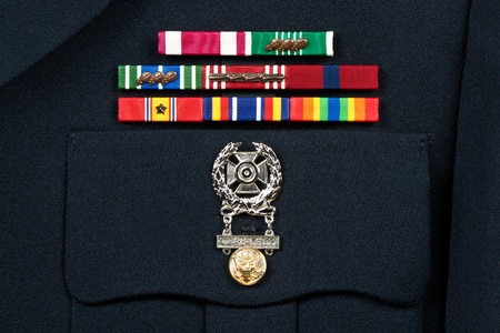 Service award ribbons and marksman badge on U.S. military dress uniform.