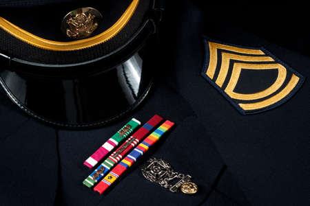war decoration: Service award ribbons and marksman badge on U.S. military dress uniform with hat and sergeants chevrons.