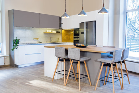 kitchen cabinets: Modern home interior. Modern kitchen design in light interior. There is also a kitchen island in the room. Kitchen and living room combined. European furniture, design, technologies.