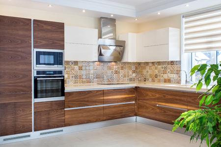 Modern home interior. Modern design of the kitchen in a light, bright interior. Kitchen wood facades are made from walnut veneer. European furniture, design, technologies.