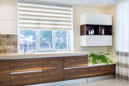 Modern home interior. Modern design of the kitchen in a light, bright interior. Kitchen wood facades are made from walnut veneer. European furniture, design, technologies.