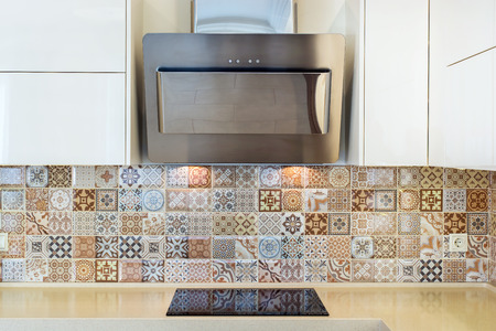 Modern home interior. Modern design of the kitchen in a bright interior. Front view. View of cooker hood, stove, wall tiles. European furniture, design, technologies.