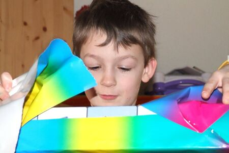 A boy opens a packet. He is seven years old. Stock Photo