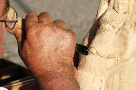 a craftsman makes from wood a sculpture Stock Photo