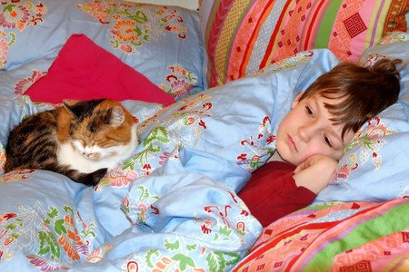 a boy and a cat in a bed