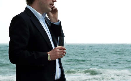 a man with a telephone. he talks. in the other hand a glas. in background the sea