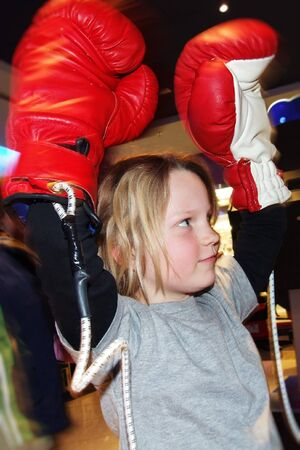 a girl in winner position with boxing gloves Stock Photo