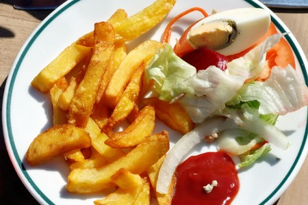 a plate with french-fries, ketchup and salad
