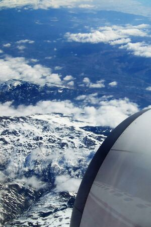 view from a plane outside. clouds. pieces from the plane are visible