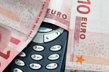 indebtedness: un telefono cellulare sotto il denaro