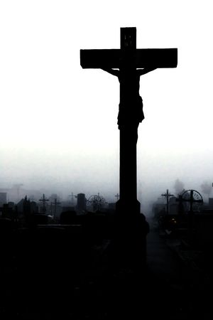 on a graveyard. a big crucifix in the middle