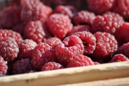 raspberries. a little piece from a wooden box is visible