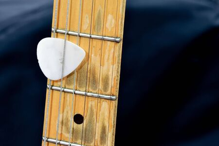 the neck from an electric guitar. between the strings is a plectron Stock Photo