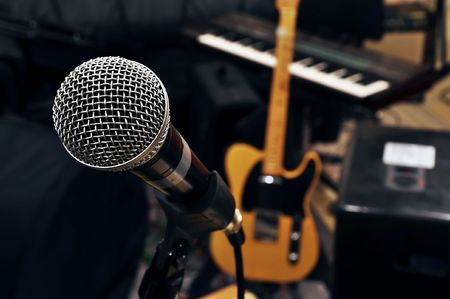 in a rehearsal room from a pop band. a microphone in the front. in the background a guitar and a keyboard are visible