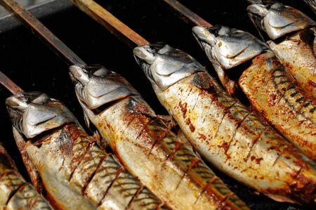 mackerel with wooden spit on a barbecue