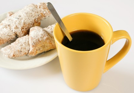a cup of coffee with a spoon. on a plate two cakes