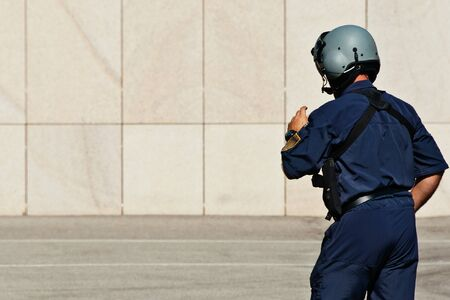 A helicopter-pilot of the police from the back. He is in his working clothes
