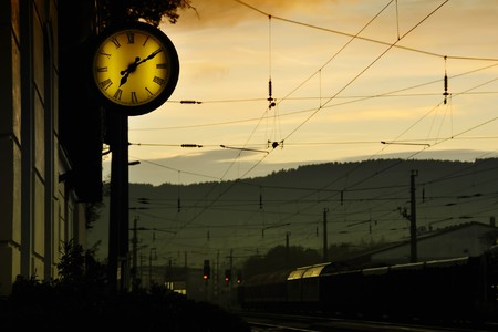 At a railway station. It is early in the morning. A clock is to be seen.